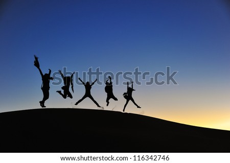 jump people silhouette dune morocco dessert - stock photo