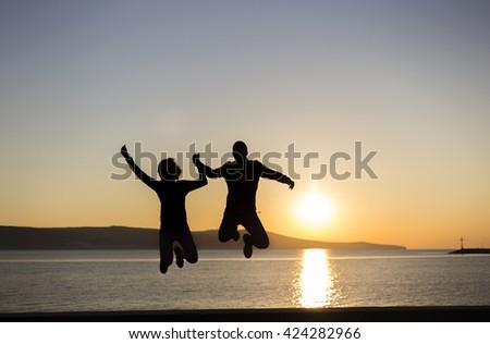 Jumping around sunrise - stock photo