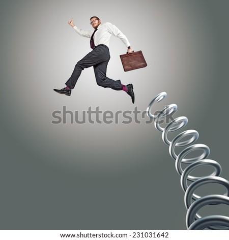 jumping businessman and huge metal springer - stock photo