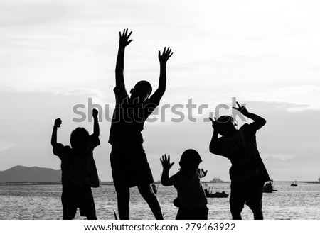 jumping child silhouette action in background sea view,fun and enjoy action   - stock photo