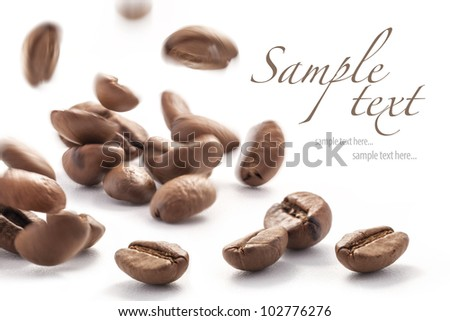 Jumping coffee beans, isolated on white background (with sample text) - stock photo