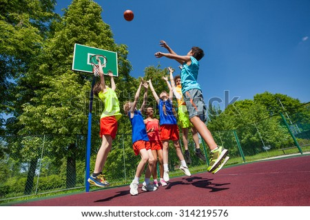 Jumping for ball teenagers playing basketball game - stock photo