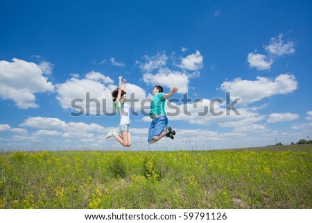 Jumping happy couple on summer field