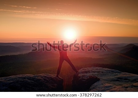 Jumping hiker in black celebrate triumph between two rocky peaks. Wonderful daybreak. Vivid and strong vignetting effect.