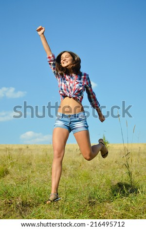 jumping joy: sexy pretty girl in jeans shorts running high and happy smiling on blue sky outdoors copy space background, portrait - stock photo