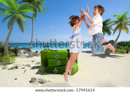 Jumping kids on a beach with a pile of luggage - stock photo