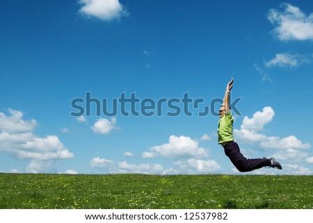 jumping man on green field - stock photo