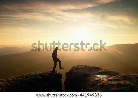 Jumping man. Young man makes jump on colorful sky background in mountains. heavy orange mist in deep valley. Miracle of nature