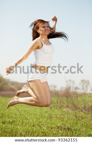 Jumping mid adult woman against summer meadow in summer day