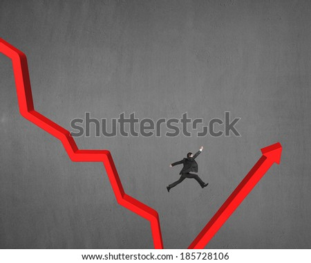 Jumping over gap on red arrow concrete wall background - stock photo