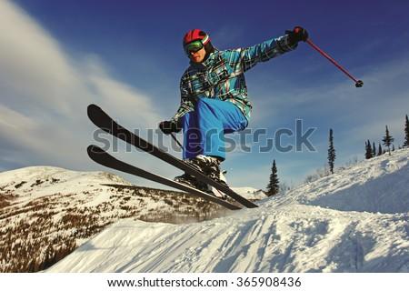 Jumping skier at jump inhigh mountains at sunny day - stock photo