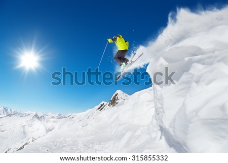 Jumping skier at jump with alpine high mountains - stock photo