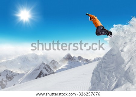 Jumping snowboarder at jump with alpine high mountains - stock photo