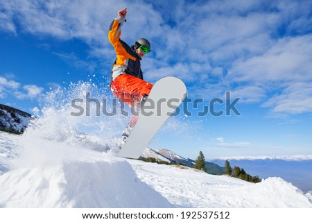 Jumping snowboarder from hill in winter - stock photo