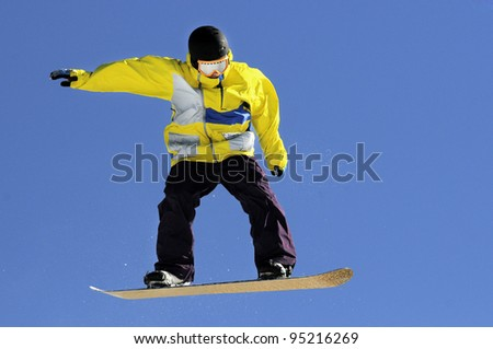 jumping snowboarder in yellow jacket against a blue sky
