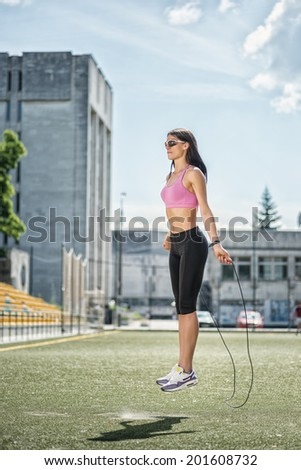 Jumping up. Young and charming woman in sunglasses and sportswear standing on the football field and jumps on the rope side view - stock photo