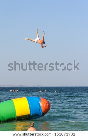 Jumping with inflatable water catapult balloon on the sea shore - stock photo