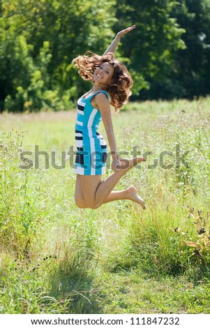 Jumping   woman against summer meadow in summer day - stock photo