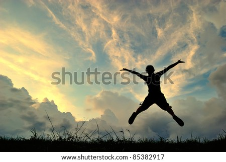 Jumping woman and sunset silhouette - stock photo