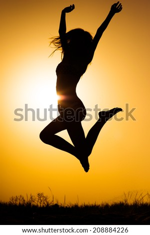 Jumping woman on the beach - stock photo