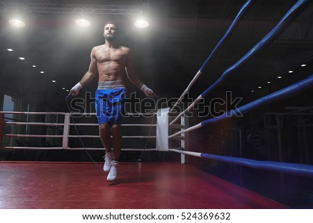Jumping young man in boxing ring