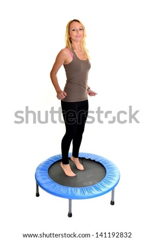jumping young woman on the trampoline, white background - stock photo