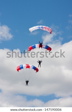jumps from a parachute in beautiful blue sky