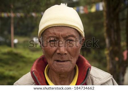 JUNBESI, NEPAL - CIRCA OCTOBER 2013: Nepalese man during a prayer at one of the monasteries circa October 2013 in Junbesi. - stock photo