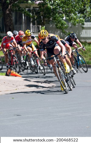 JUNE 15, 2014: Cyclist leads pack around turn at final stage of 2014 North Star Grand Prix in Stillwater, Minnesota. About 300 top pro cyclists from around the world compete in the prestigious event.  - stock photo