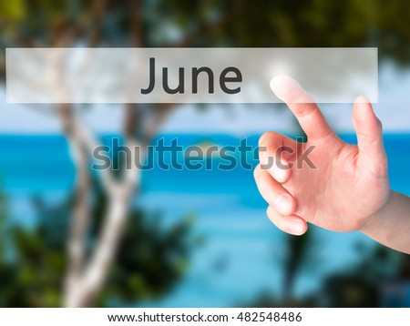 June - Hand pressing a button on blurred background concept . Business, technology, internet concept. Stock Photo