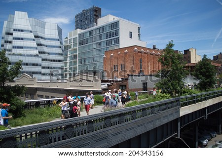 June 20, 2014 - New York, USA: Visitors walk on a path on the High Line. The High Line Park in New York City was created atop an abandoned elevated freight rail line. - stock photo