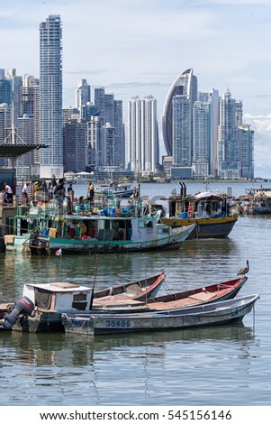 June 15, 2016 Panama City, Panama: small fishing boats floating on the water by the fish market with the modern downtown highrise buildings in the background