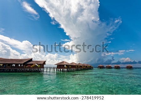 JUNE 27, 2008 - SABAH, MALAYSIA: Wooden chalet resorts cater for tourists visiting Mabul Island in Sabah. This island is situated next to Sipadan, a world famous scuba diving site. - stock photo