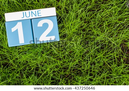 June 12th. Image of june 12 wooden color calendar on green grass lawn background. Summer day, empty space for text. - stock photo