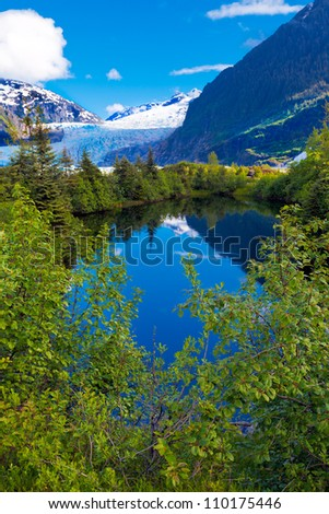 Juneau, Alaska beautiful deep blue lake with reflections of trees and mountains, and the Mendenhall Glacier in the background - stock photo