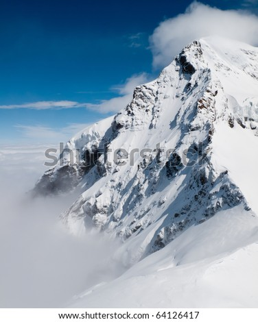 Jungfraujoch in Swiss Alps showing station and distant peaks above clouds - stock photo