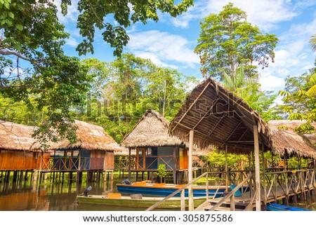 Jungle shacks on stilts in the Amazon rain forest near Iquitos, Peru - stock photo