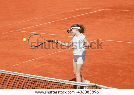 Junior female tennis player hits forehand. Girl in focus, racket and ball in motion blur.  - stock photo