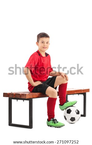 Junior football player in a red jersey sitting on a bench with a ball under his foot isolated on white background - stock photo