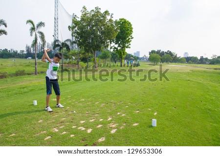 Junior golfer driving golf ball on golf course - stock photo