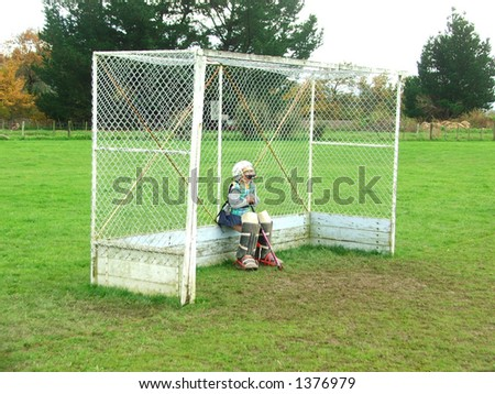 Junior hockey goalkeep,sitting down waiting for action