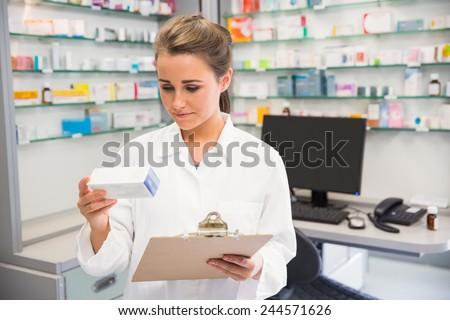 Junior pharmacist holding medicine box at the hospital pharmacy - stock photo