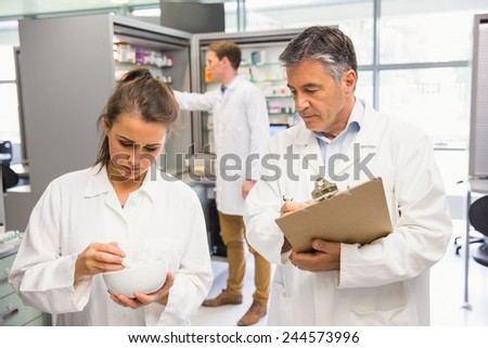 Junior pharmacist mixing a medicine being supervised at the hospital pharmacy - stock photo