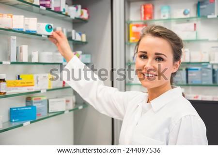 Junior pharmacist taking medicine from shelf at the hospital pharmacy - stock photo