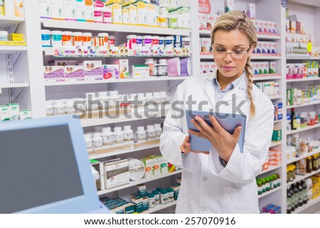 Junior pharmacist using tablet pc in the pharmacy - stock photo