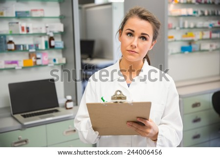 Junior pharmacist writing on clipboard at the hospital pharmacy - stock photo
