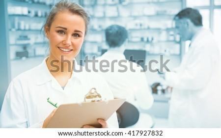 Junior pharmacist writing on clipboard at the hospital pharmacy - stock photo