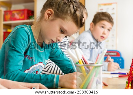 Junior pupils drawing with highlighters - stock photo