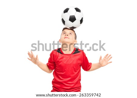 Junior soccer player wearing red shirt joggling with a soccerball isolated on white background - stock photo