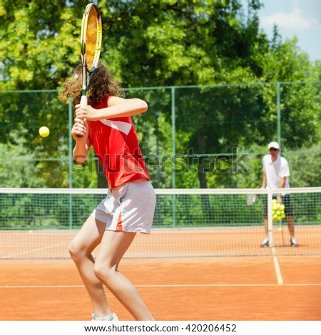 Junior tennis player in training with coach, practicing backhand - stock photo